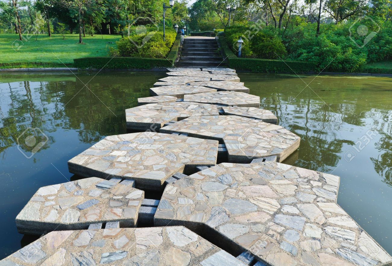 stone path across the pond in the park stock photo picture and