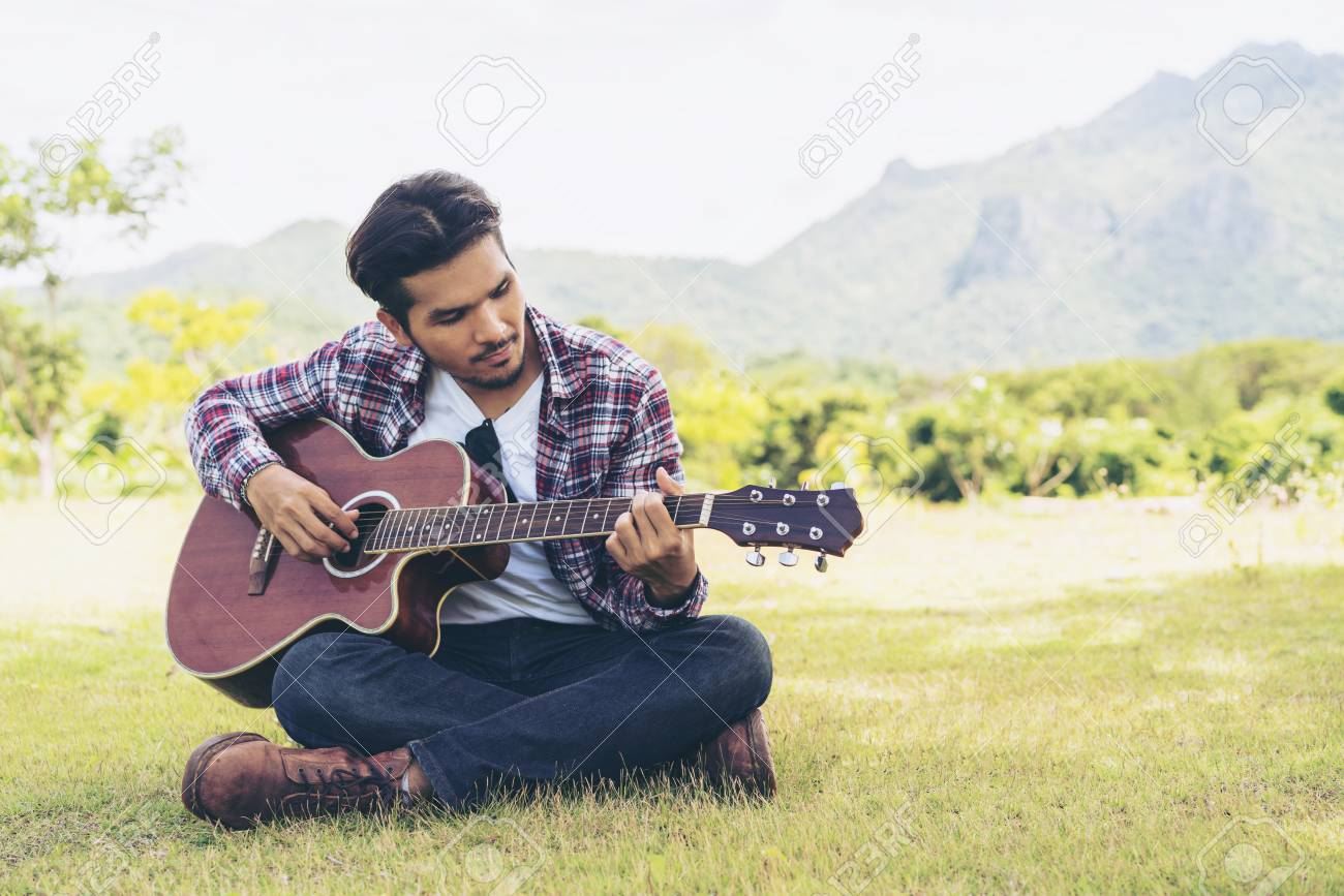 Handsome man playing guitar, sitting on green grass  Nature