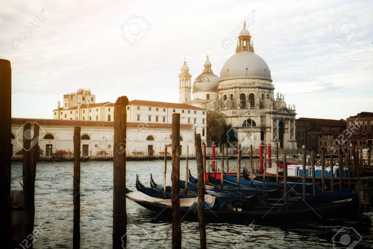 Gondola boats in Venice Italy with gorgeous view of Basilica Santa Maria della Salute. Venice is famous travel destination in Italy for its unique cityscape and culture. - 102483110