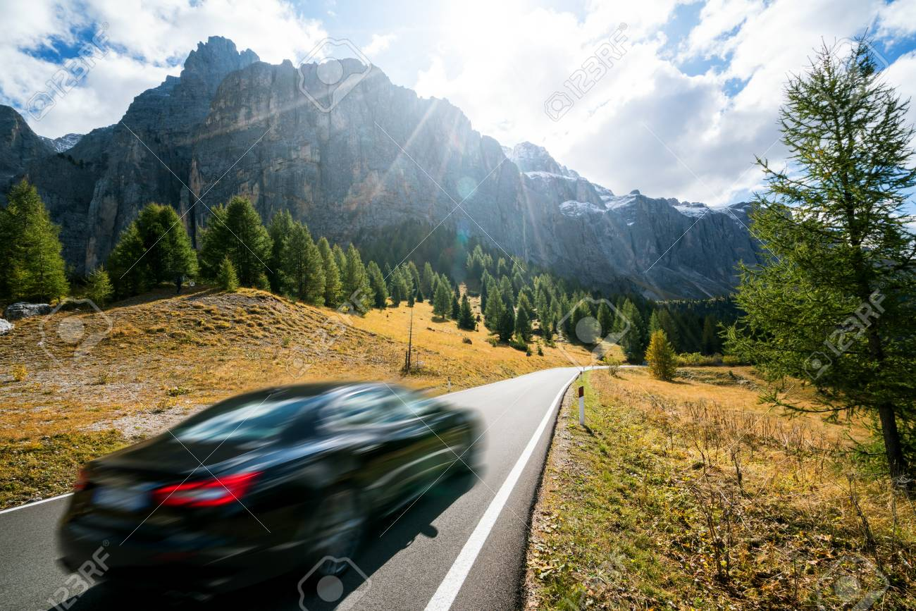 Car Driving On Beautiful Mountain Road With Trees, Forest And Mountains In  The Backgrounds. Taken At State Highway Road In Passo Gardena, Sella  Mountain Group Of Dolomites Mountain In Italy. Stock Photo,