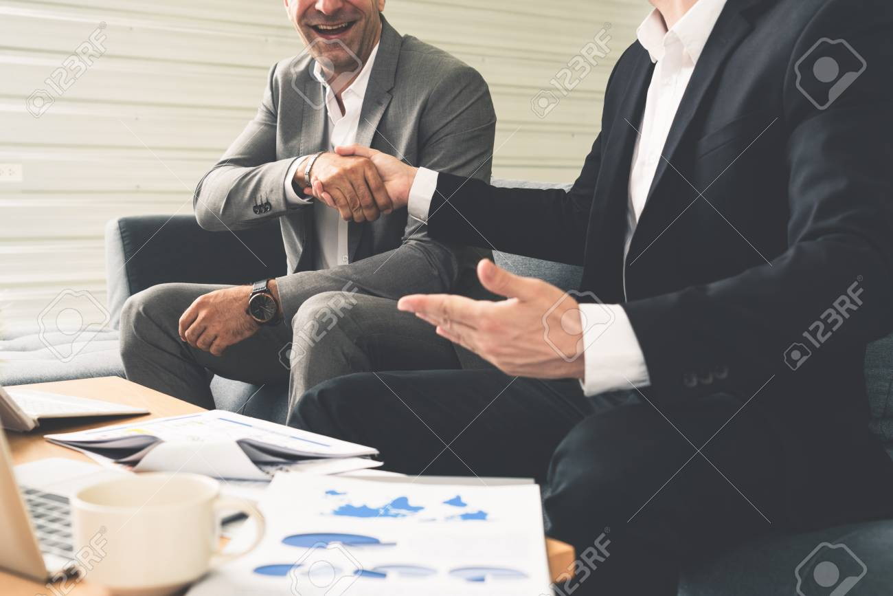 Businessman handshake with another businessman partner in modern workplace office. People corporate business deals concept. - 117350512