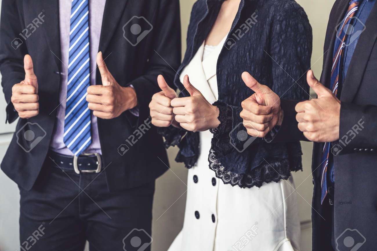 Many happy business people make thumbs up sign join hands together with joy and success. Company employee celebrate after successful work project. Corporate partnership and achievement concept. - 121834790