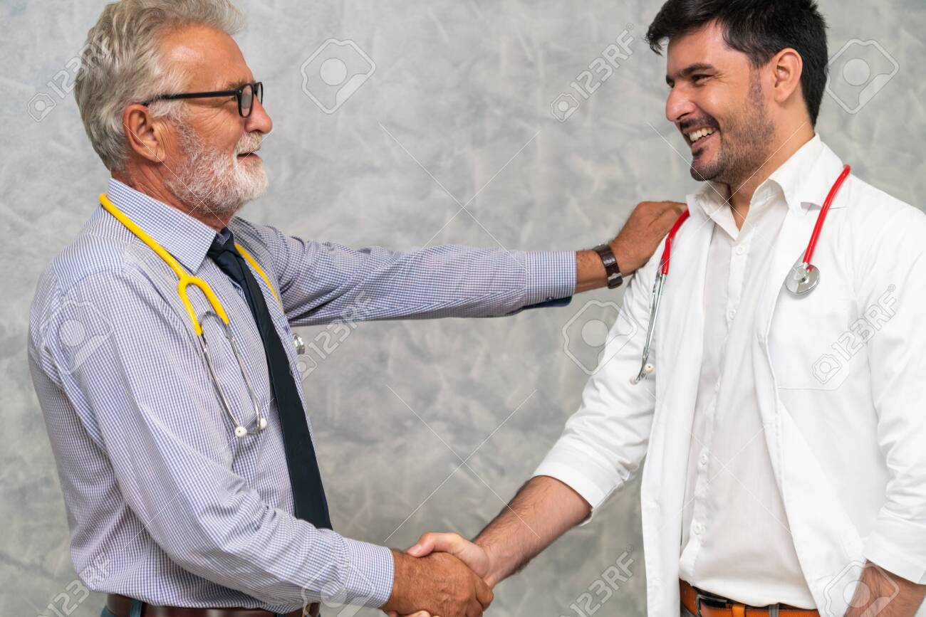 Doctor in hospital handshake with another doctor. Healthcare people teamwork and medical staff service concept. - 119874731