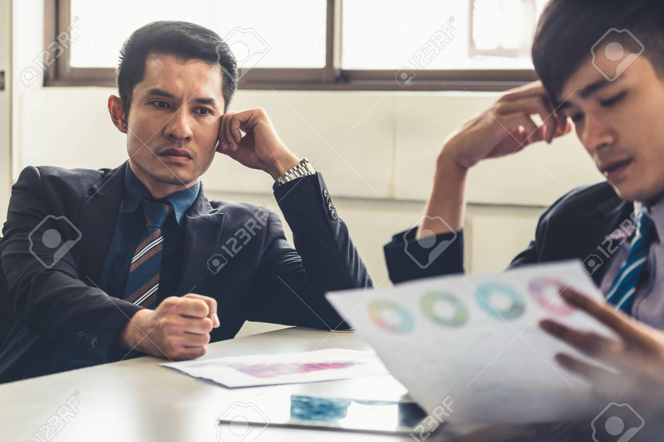 Unhappy business manager and young businessman partner in meeting room at the office. They are under stress because of bad financial document report. Company crisis concept. - 120256404
