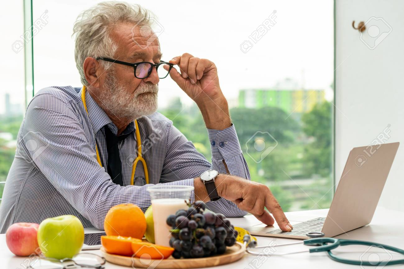 Senior male nutritionist doctor working with laptop computer on table in the hospital office. Dieting and healthy eating concept. - 120800835
