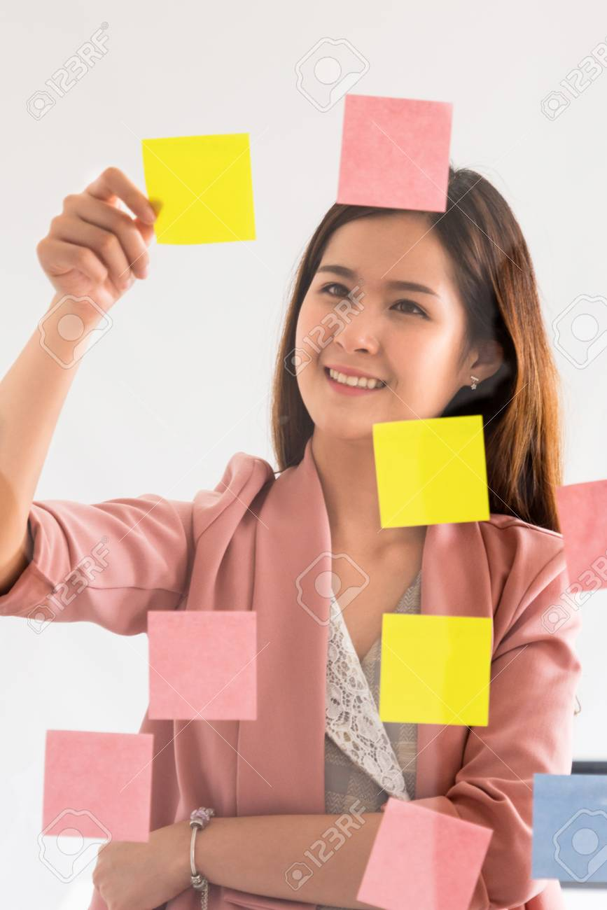 Happy businesswoman thinking creative ideas with sticky notes on glass wall at the office. Work planning and education concept - 121166560