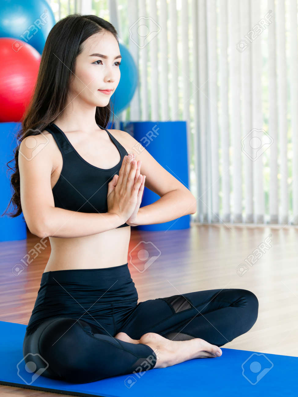 Young woman practicing yoga position in an indoor gym studio. Healthy and wellness lifestyle concept. - 121169294