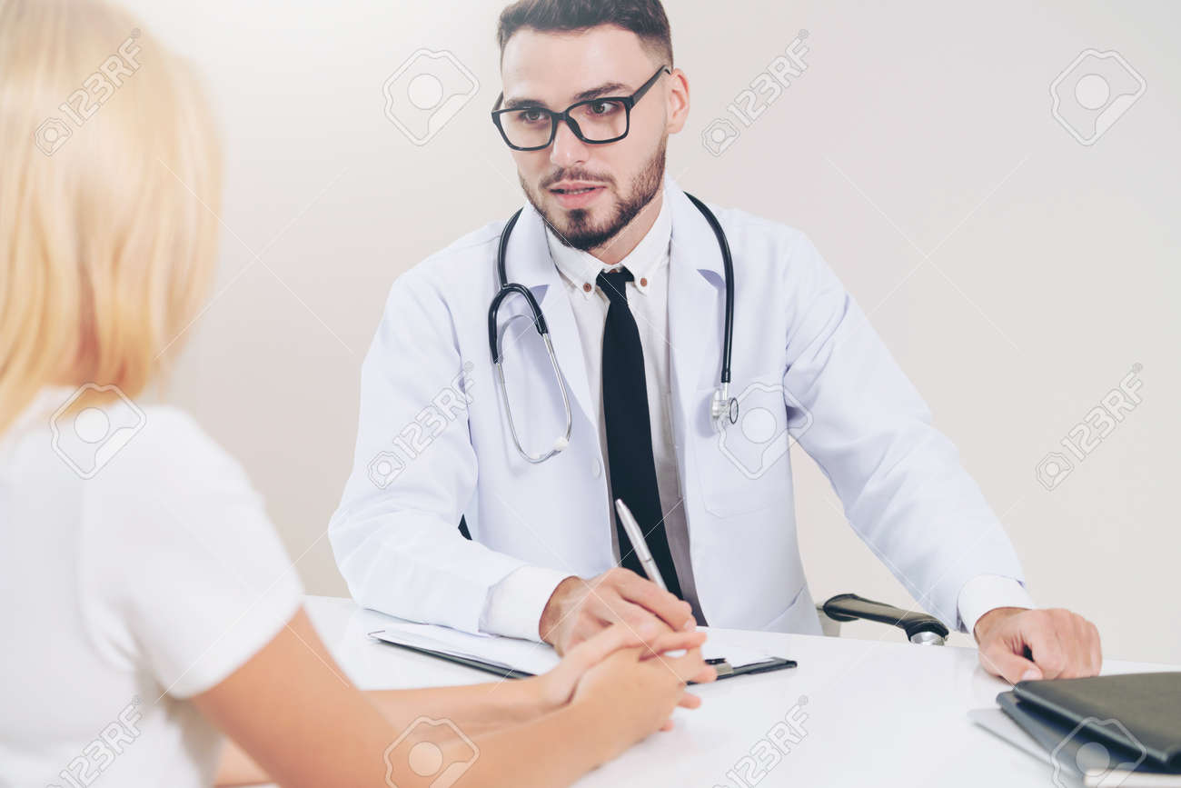 Male doctor is talking to female patient in hospital office. Healthcare and medical service. - 121491142