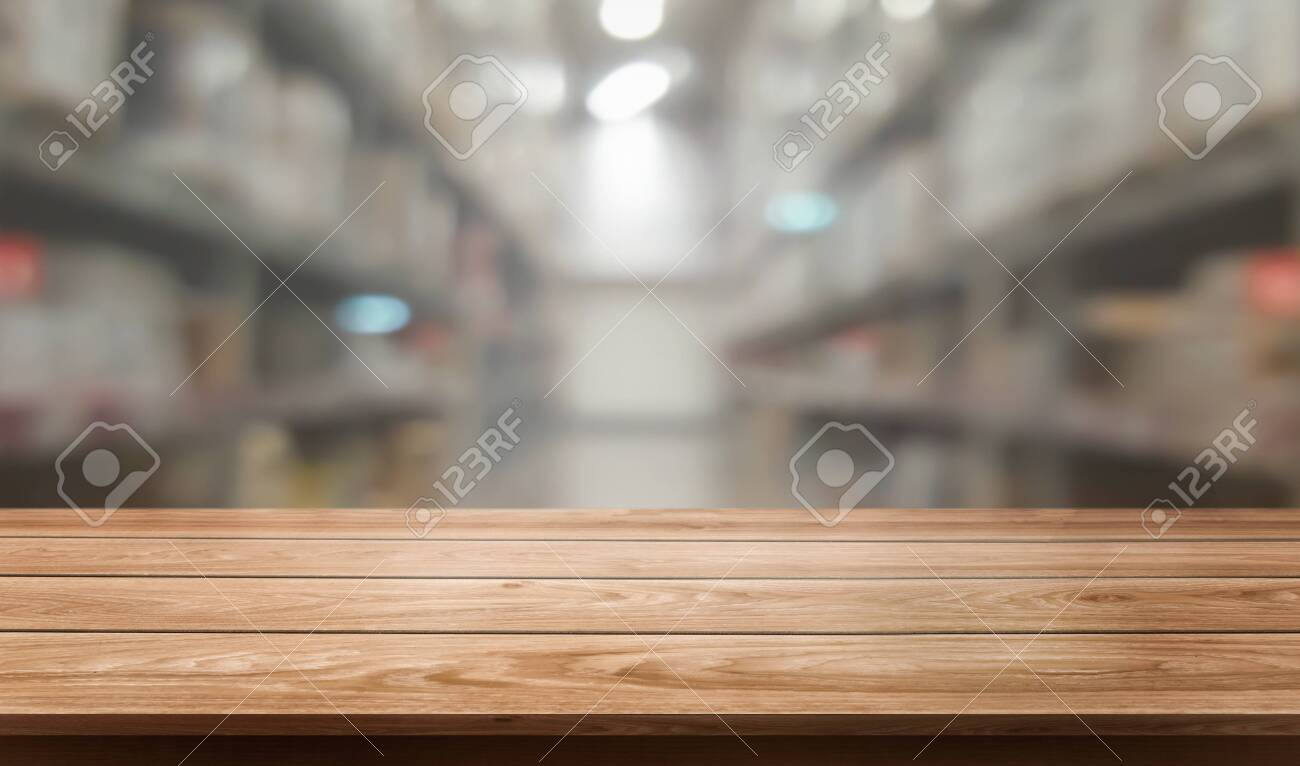 Wood table in warehouse storage blur background with empty copy space on the table for product display mockup. Hardware goods distribution and industrial logistics concept. - 128879331