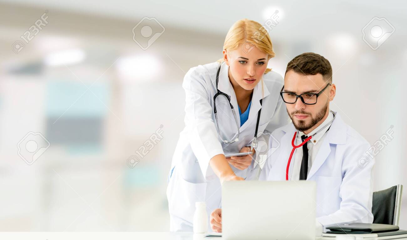 Doctor working with laptop computer at the office while having discussion with another doctor in the hospital. Medical healthcare and doctor service. - 128430624
