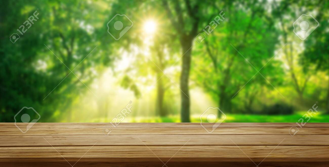 Brown wood table in green blur nature background of trees and grass in the park with empty copy space on the table for product display mockup. Fresh spring and natural product concept. - 128482972