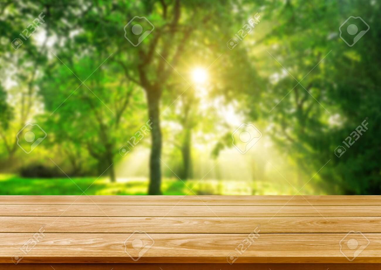 Brown wood table in green blur nature background of trees and grass in the park with empty copy space on the table for product display mockup. Fresh spring and natural product concept. - 128482990