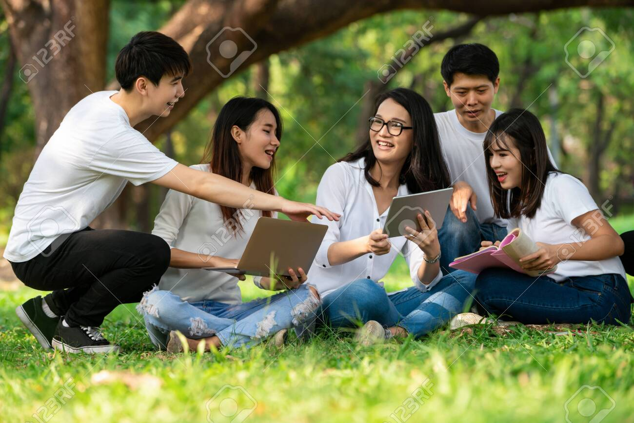 Team of young students studying in a group project in the park of university or school. Happy learning, community teamwork and youth friendship concept. - 134515359
