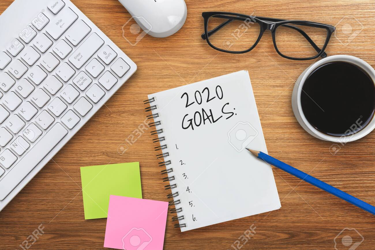 New Year Resolution Goal List 2020 - Business office desk with notebook written in handwriting about plan listing of new year goals and resolutions setting. Change and determination concept. - 133535055