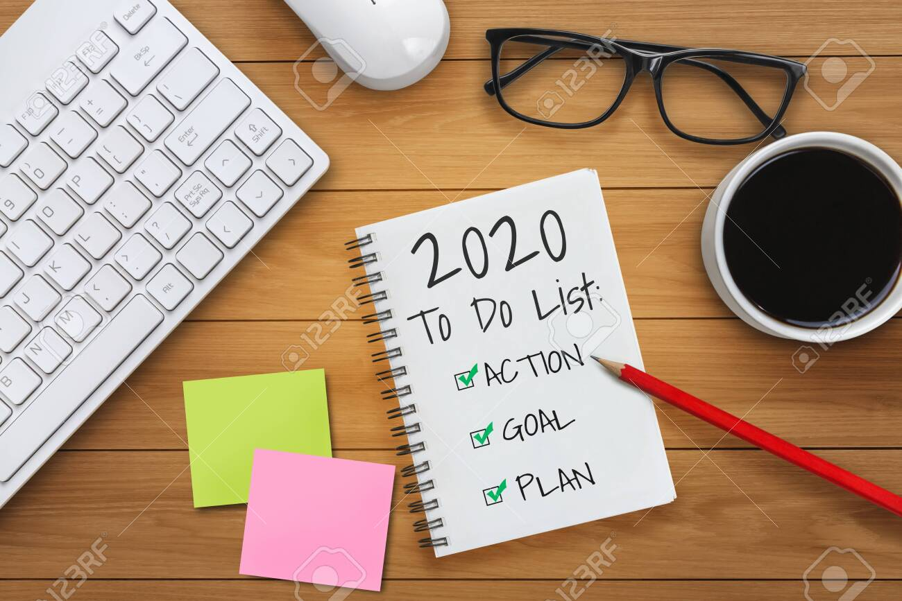 New Year Resolution Goal List 2020 - Business office desk with notebook written in handwriting about plan listing of new year goals and resolutions setting. Change and determination concept. - 133534648