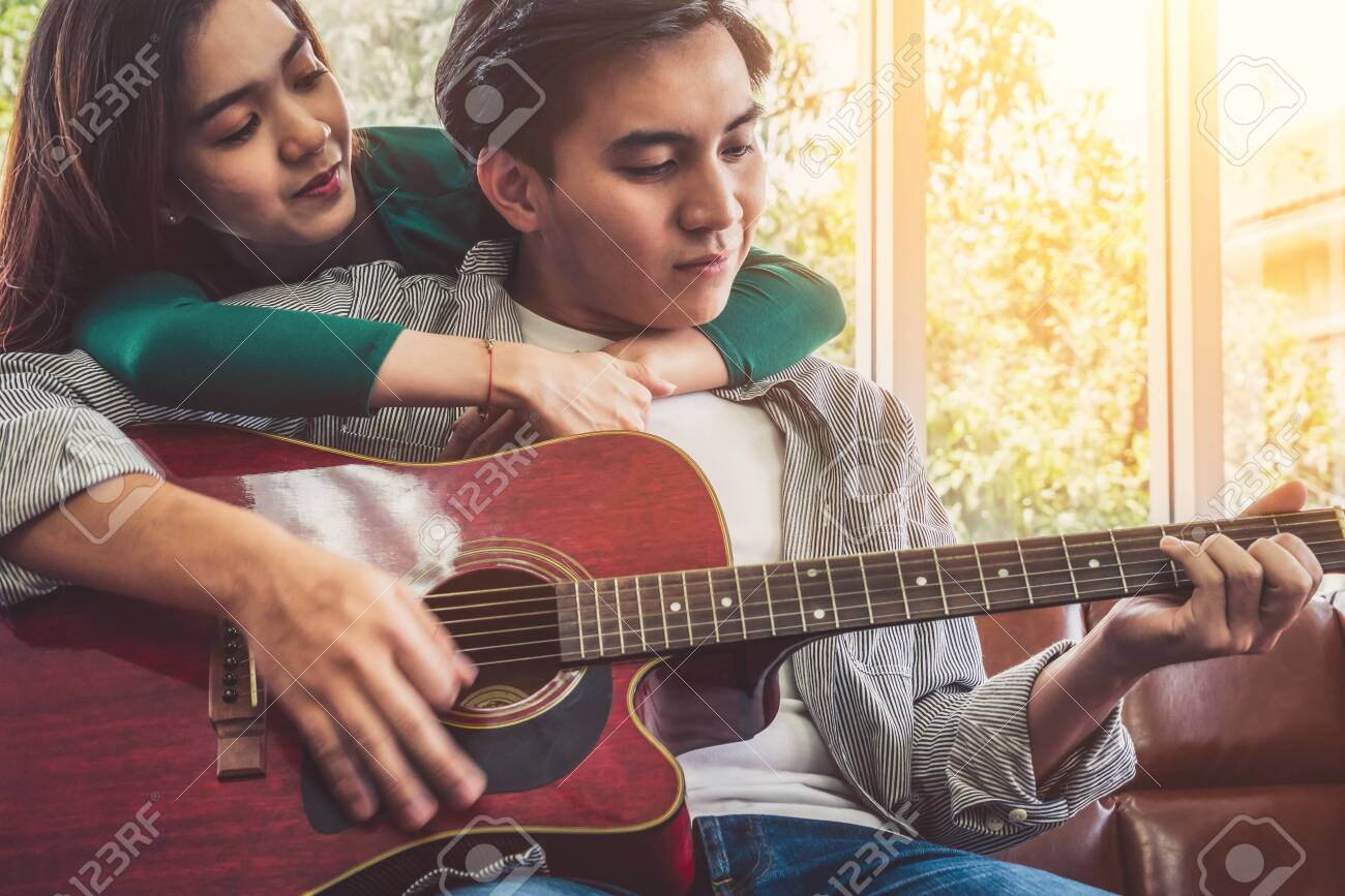 Young Asian Couple Plays Guitar and Sing Song in Living Room at Home Together. Music and Lifestyle concept. - 144484796