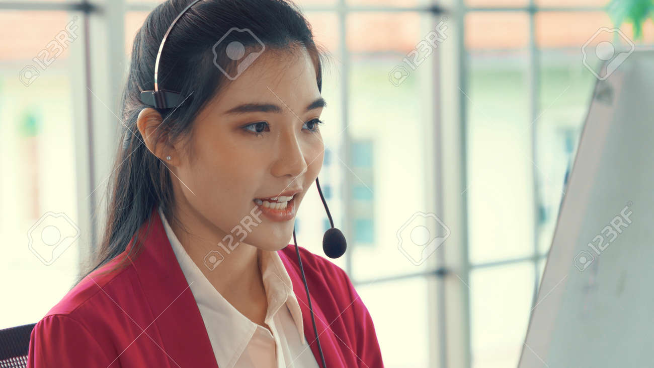 Businesswoman wearing headset working actively in office . Call center, telemarketing, customer support agent provide service on telephone video conference call. - 171940861