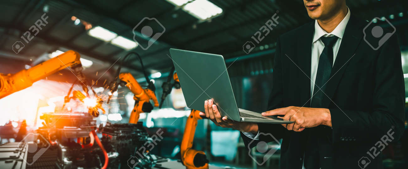 Engineer use advanced robotic software to control industry robot arm in factory . Automation manufacturing process controlled by specialist using IOT software connected to internet network . - 171932150