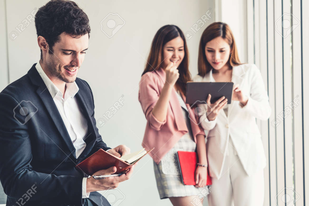 Happy young handsome businessman reading book and working in office with colleagues and friend at workplace. Corporate business people group. - 171925065