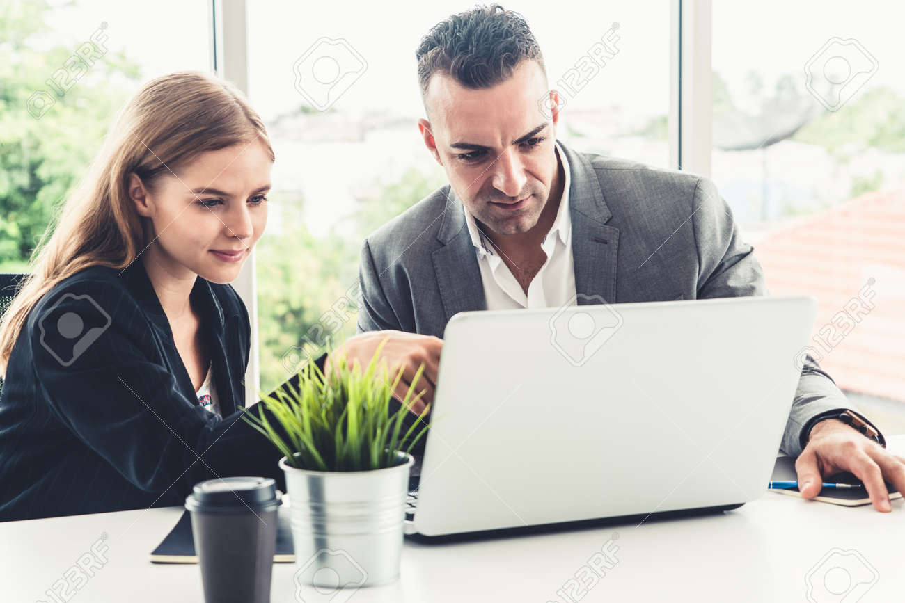 Businessman executive is in meeting discussion with a businesswoman worker in modern workplace office. People corporate business team concept. - 171925676