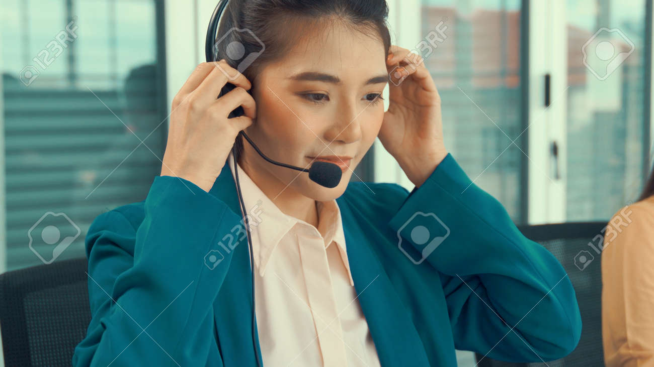 Businesswoman wearing headset working actively in office . Call center, telemarketing, customer support agent provide service on telephone video conference call. - 171932154