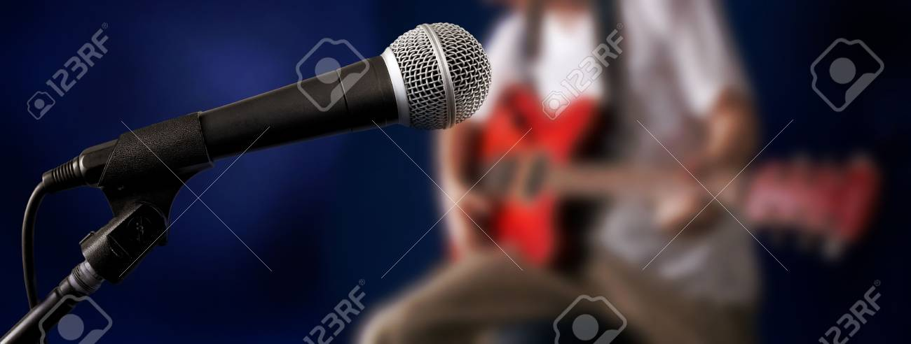 the blurry figure of guitarman and microphone at front Stock Photo - 5707398