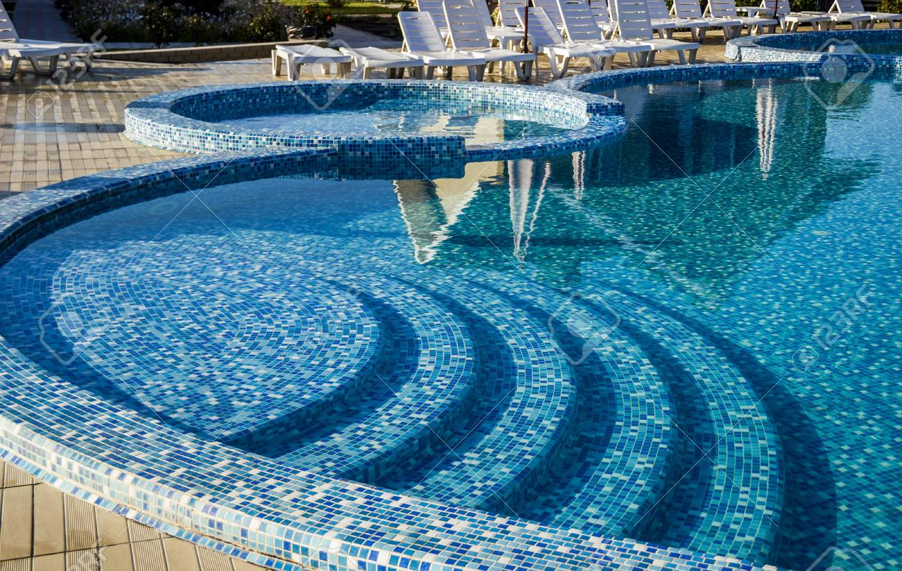 curved steps to the swimming pool with blue mosaic tiles