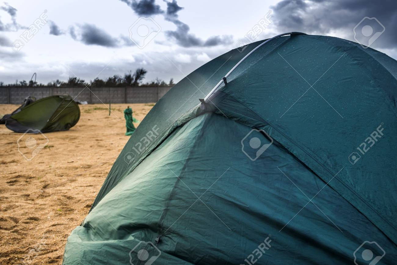 green c&ing tent on the beach at the stormy weather and broken tent at back Stock & Green Camping Tent On The Beach At The Stormy Weather And Broken ...