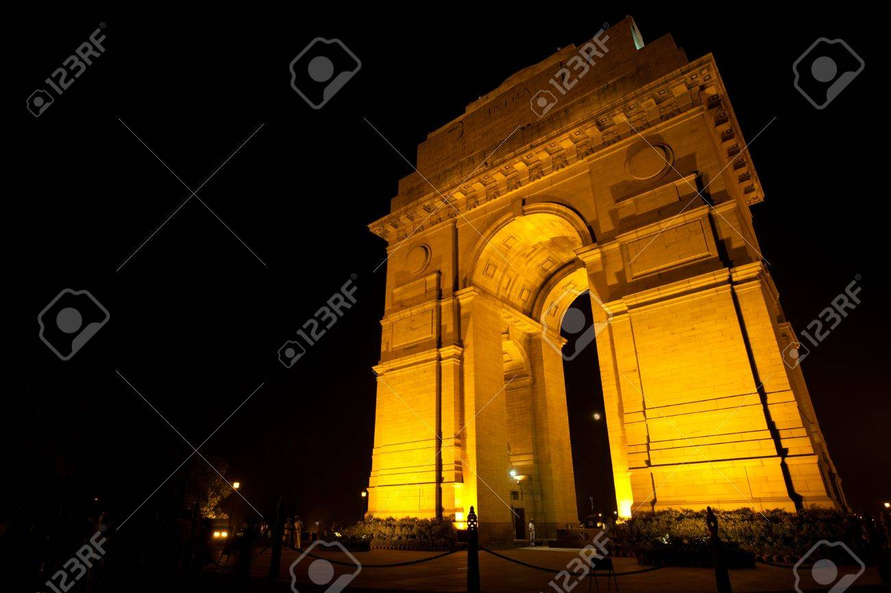 The moon is visible through Delhi's India Gate memorial, tastefully illuminated by floodlights at night - 8422722