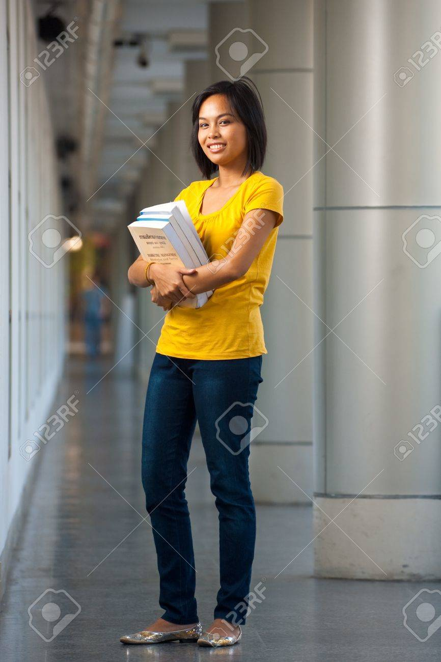 Full length portrait of a happy and smiling college student carrying books.  Young female Asian Thai model late teens, early 20s of Chinese descent. Stock Photo - 8479349