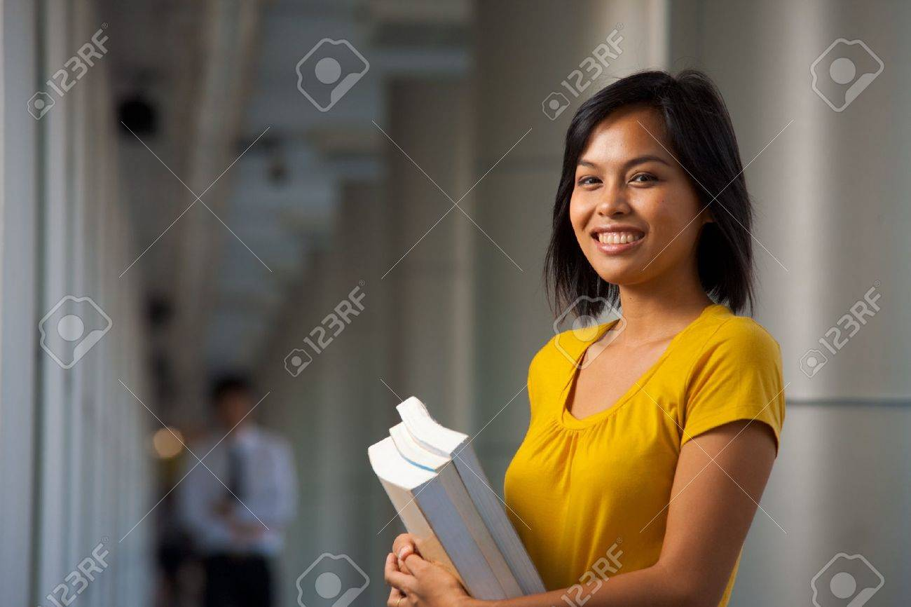 A half portrait of a cute smiling college student on a beautiful modern campus. Young female Asian Thai model late teens, early 20s of Chinese descent. - 8479355