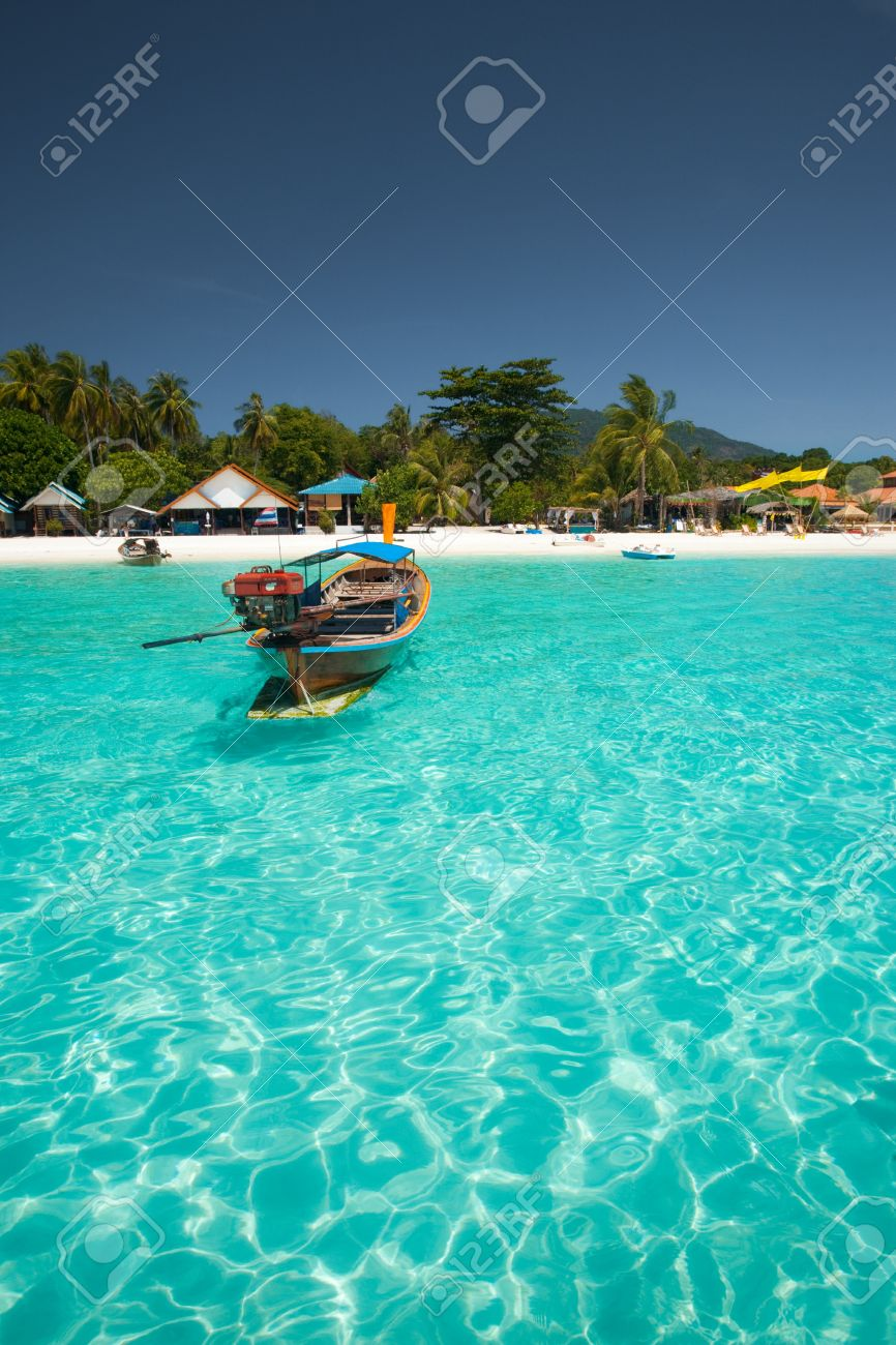 A traditional longtail boat floats in perfect crystal clear emerald blue water on the island paradise of Koh Lipe (aka Ko Lipeh), Thailand - 9549431