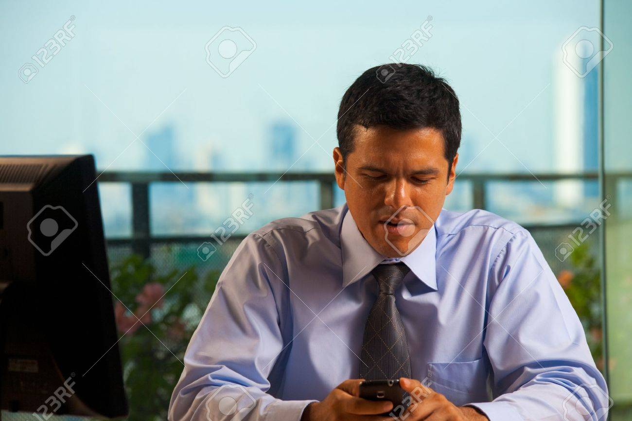A hispanic businessman receives bad news by text (sms) on his smartphone. 30s latino American male of mixed Brazilian - Mexican descent. - 9595590