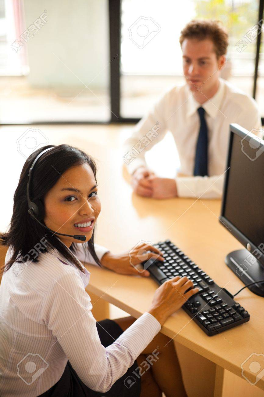 A beautiful asian customer service agent smiles while serving a customer at her desk Stock Photo - 9866997