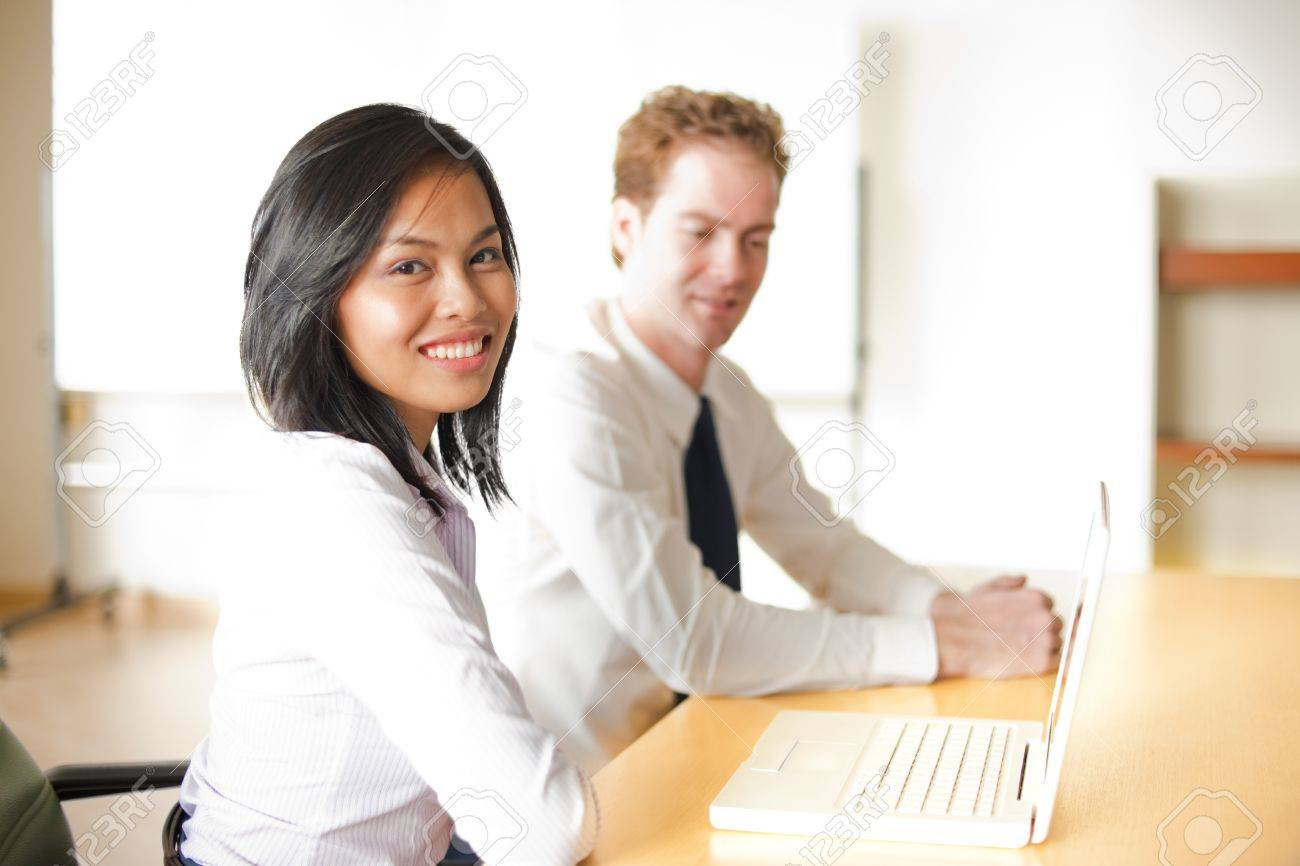 A cute corporate asian businesswoman smiles during a meeting with her caucasian colleague in front of a laptop - 9866989