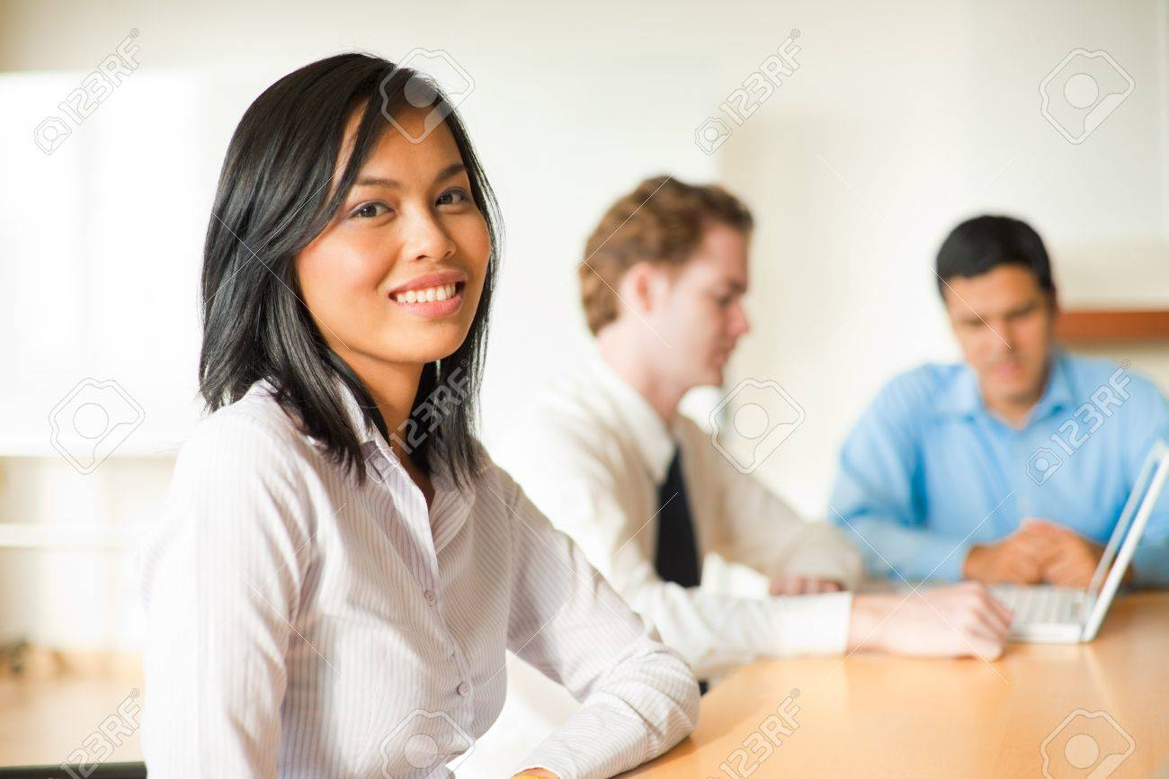 An attractive Asian businesswoman looks at the camera during a meeting with a diverse group of business people including a latino and caucasian male. - 10030748