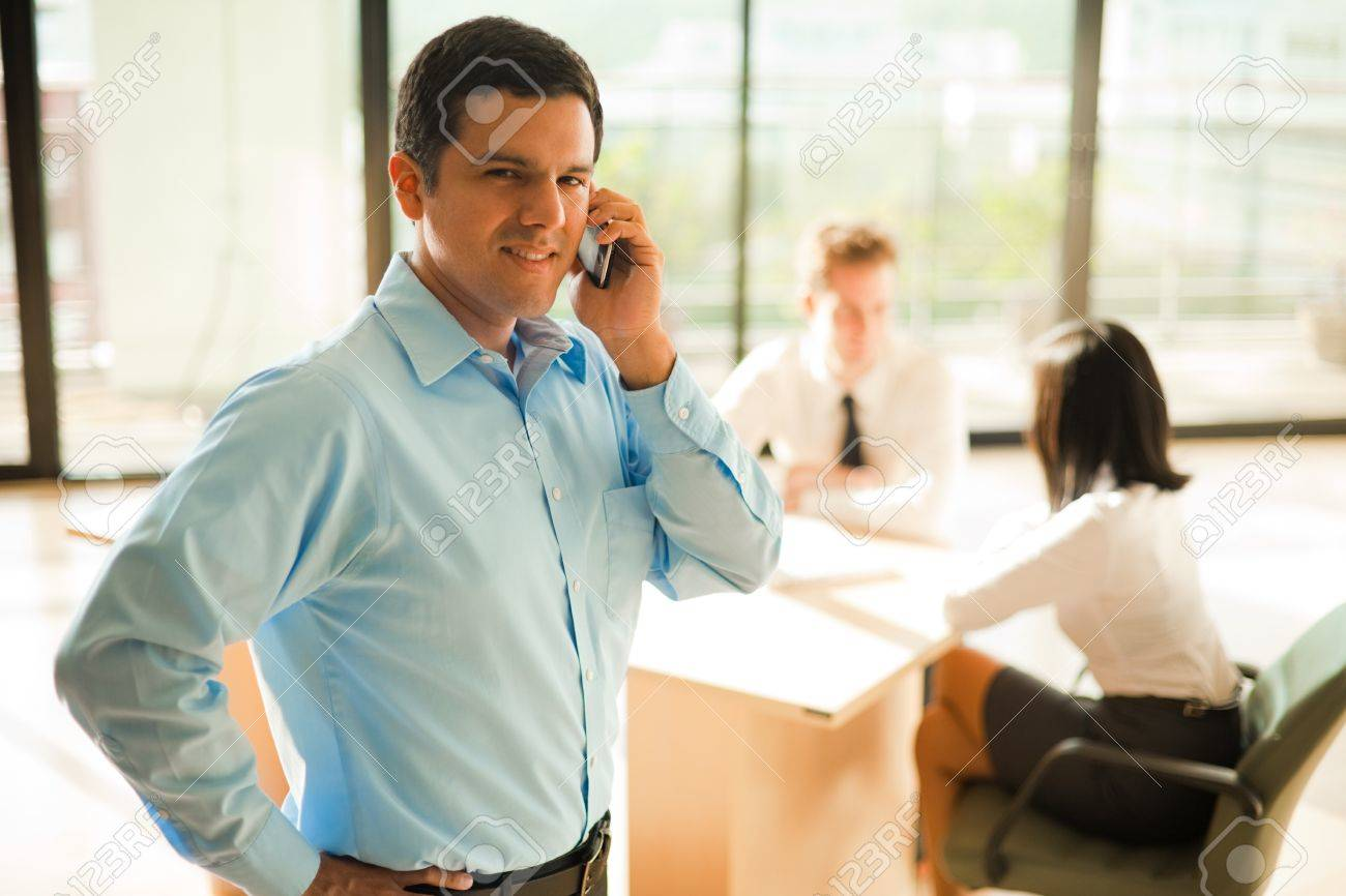 A well dressed and handsome hispanic male businessman uses a cell phone during a meeting in a bright office. Stock Photo - 10030765
