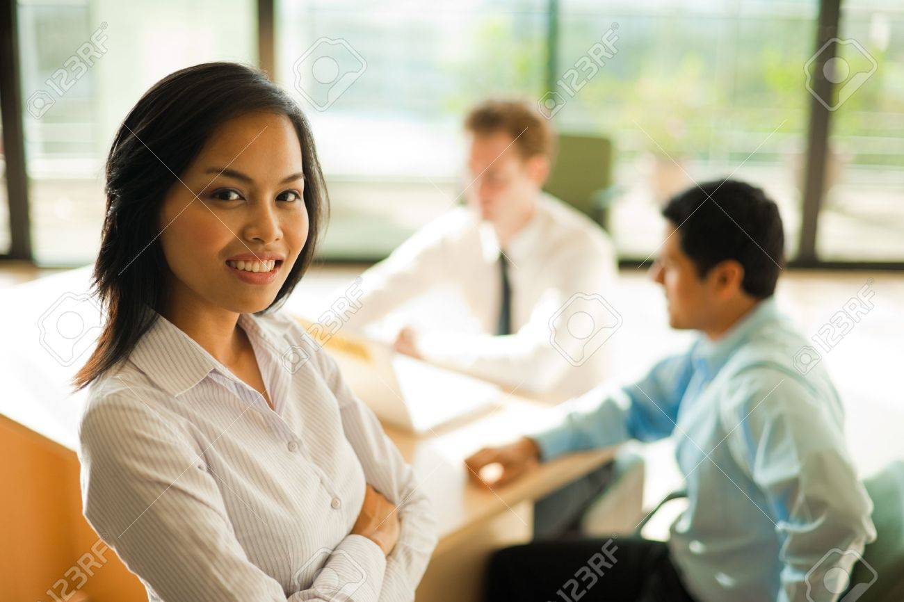 An attractive Asian female stands and looks at the camera during a business meeting. Stock Photo - 10162385