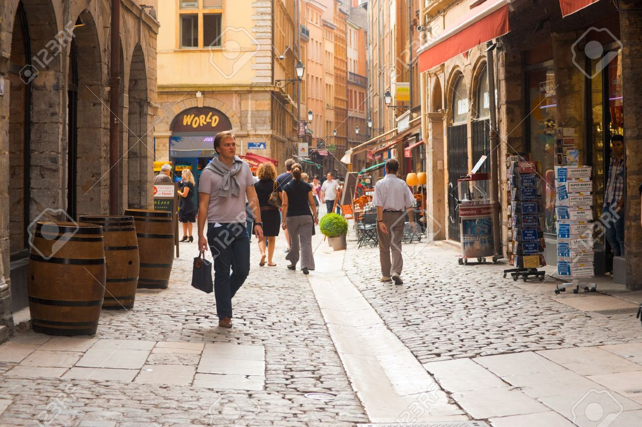 Lyon, France - June 22, 2011: Shoppers on the main pedestrian shopping street called Rue St. Jean in the old city Vieux Lyon. The street is a must-see destination for anyone visiting Lyon June 22, 2011 at Lyon France - 13257881