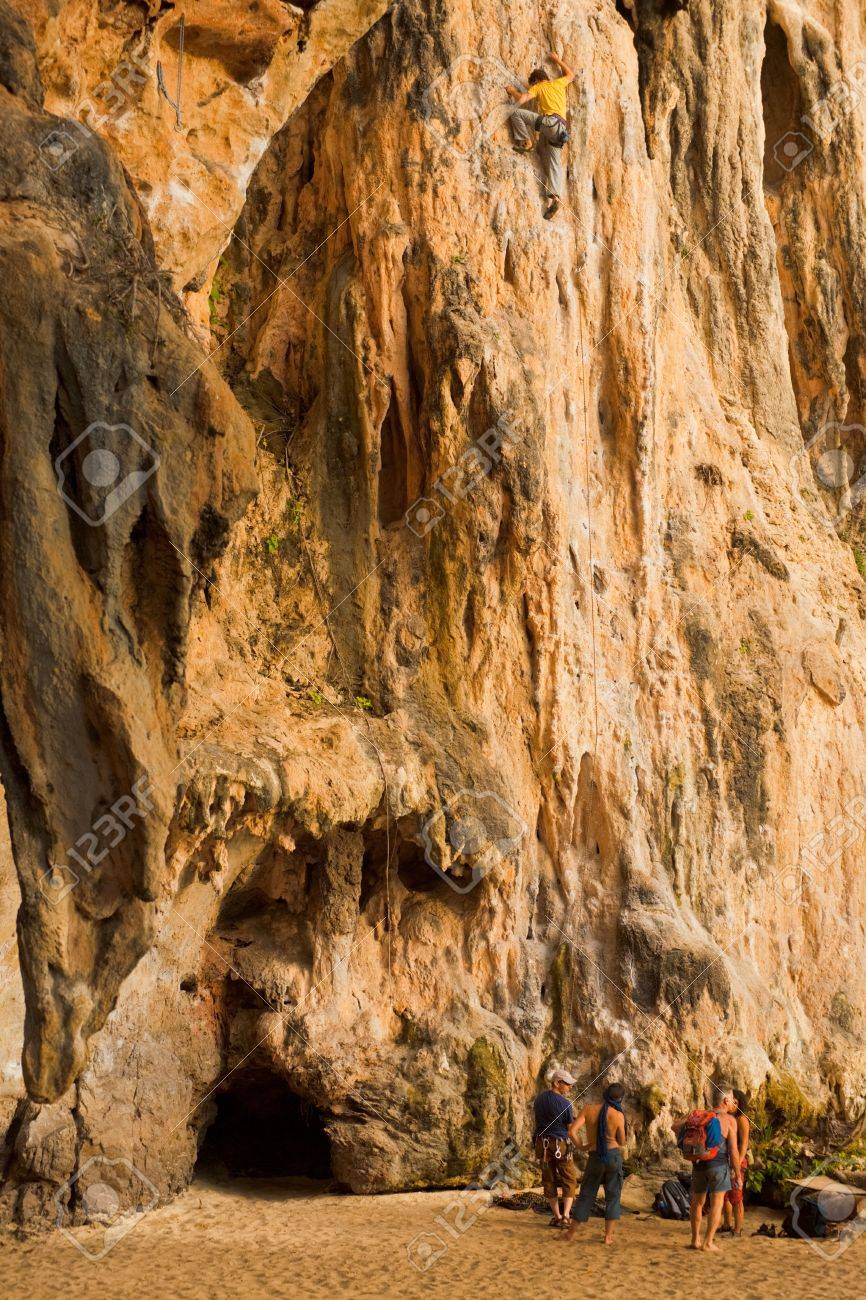 Railay Beach, Thailand - January 31, 2011: A male climber scales the face of a limestone cliff in Railay beach, a hub of rock climbing activities in Thailand January 31, 2011 at Phra Nang Railay Beach, Thailand. - 13365310