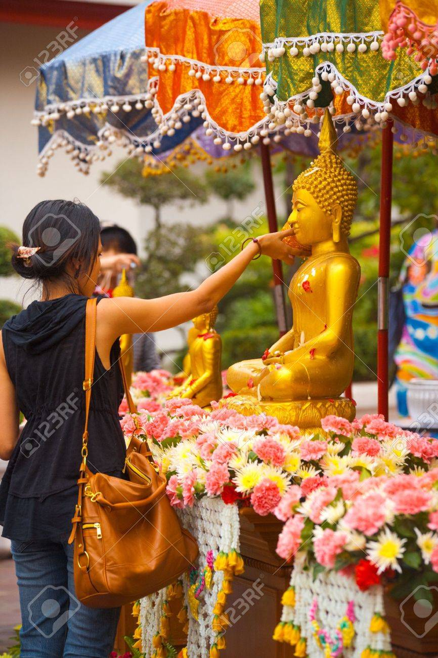 Bangkok, Thailand - April 9, 2011: A Buddha statue is cleaned with water by a young Thai woman, an annual ritual for the holiday of Songkran or Thai New Year April 9, 2011 at Bangkok, Thailand - 13365307