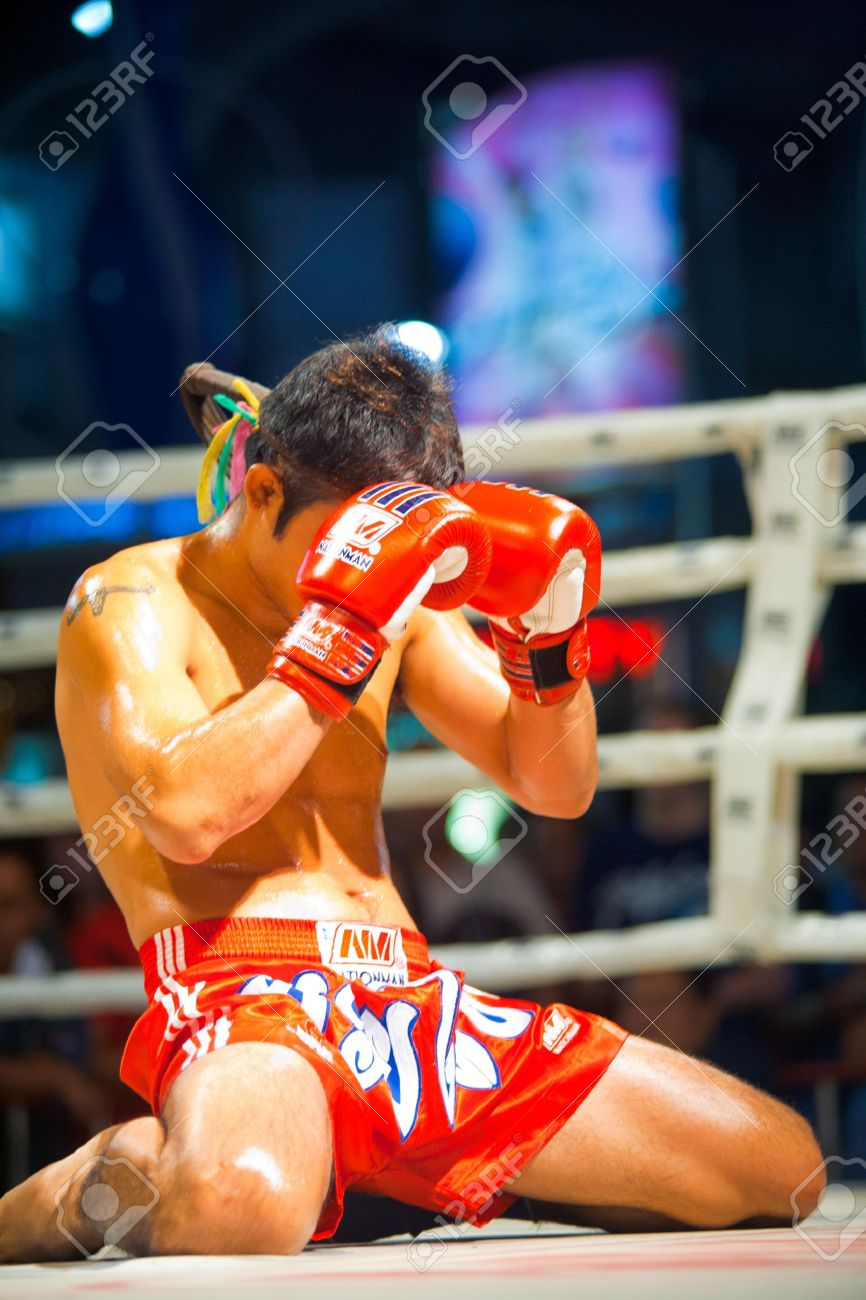 BANGKOK, THAILAND - DECEMBER 8, 2010: A muay thai kickboxer kneels and covers his face with his gloves during a pre-fight ritual called the wai khru on December 8, 2010 in Bangkok, Thailand - 13574470