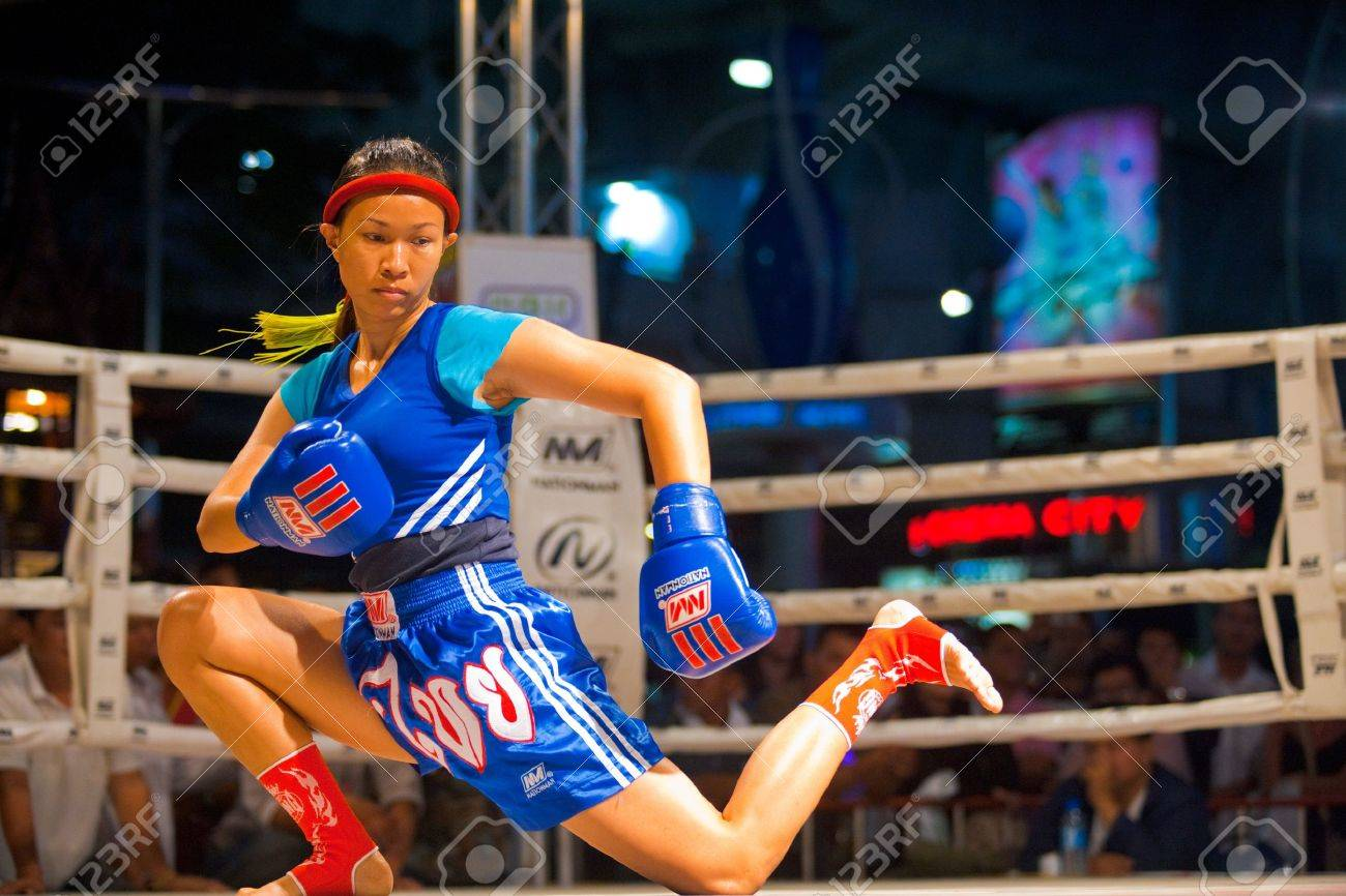 BANGKOK, THAILAND - DECEMBER 8, 2010: A female muay thai kickboxer performs a knee down kicking routine during a pre- kickboxing ritual called the wai khru on December 8, 2010 in Bangkok, Thailand - 13574472