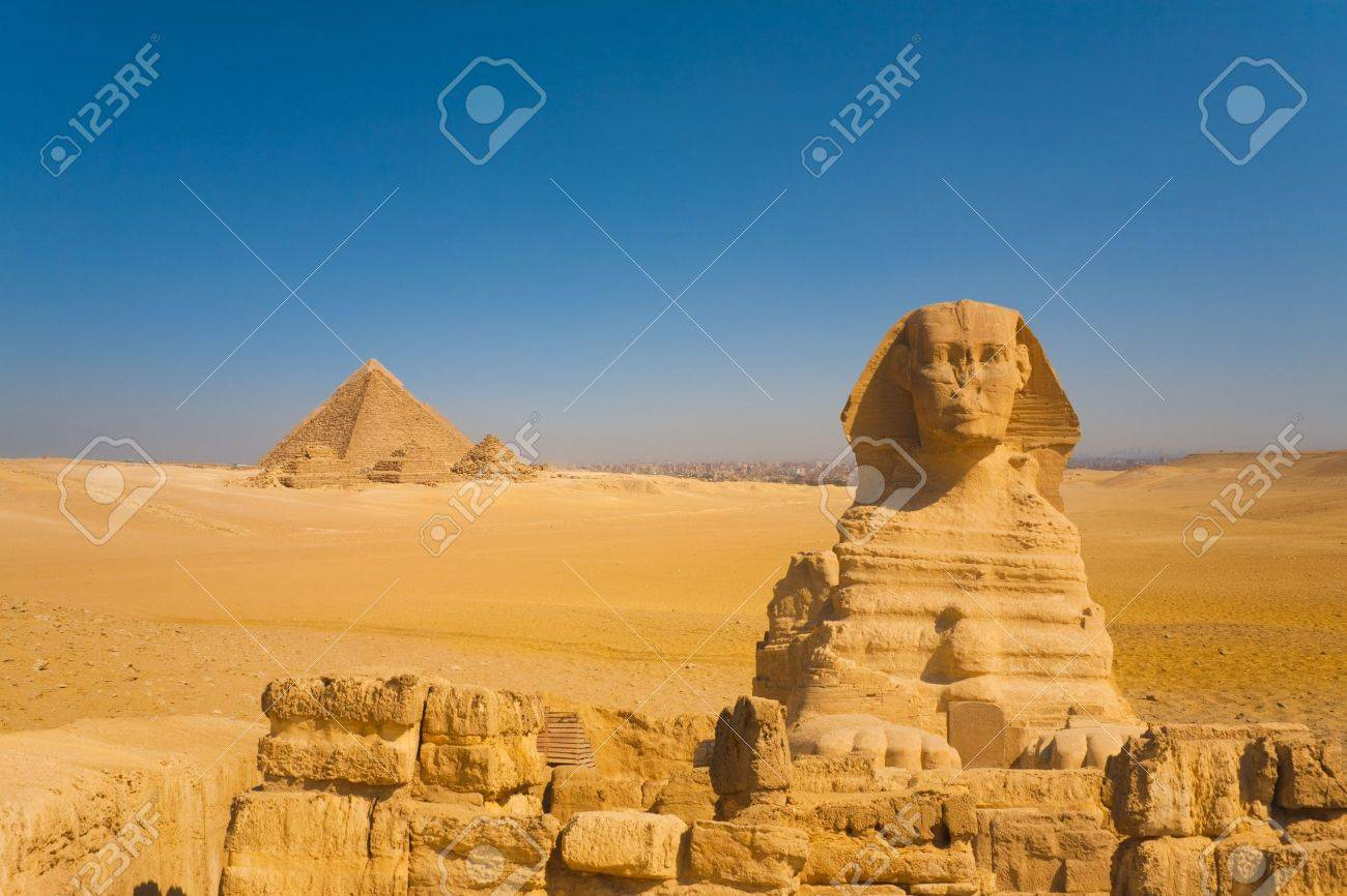 The sphinx stands guard to a distant set of Giza pyramids in a vast desert with the city of Cairo in the background, Egypt - 13699768