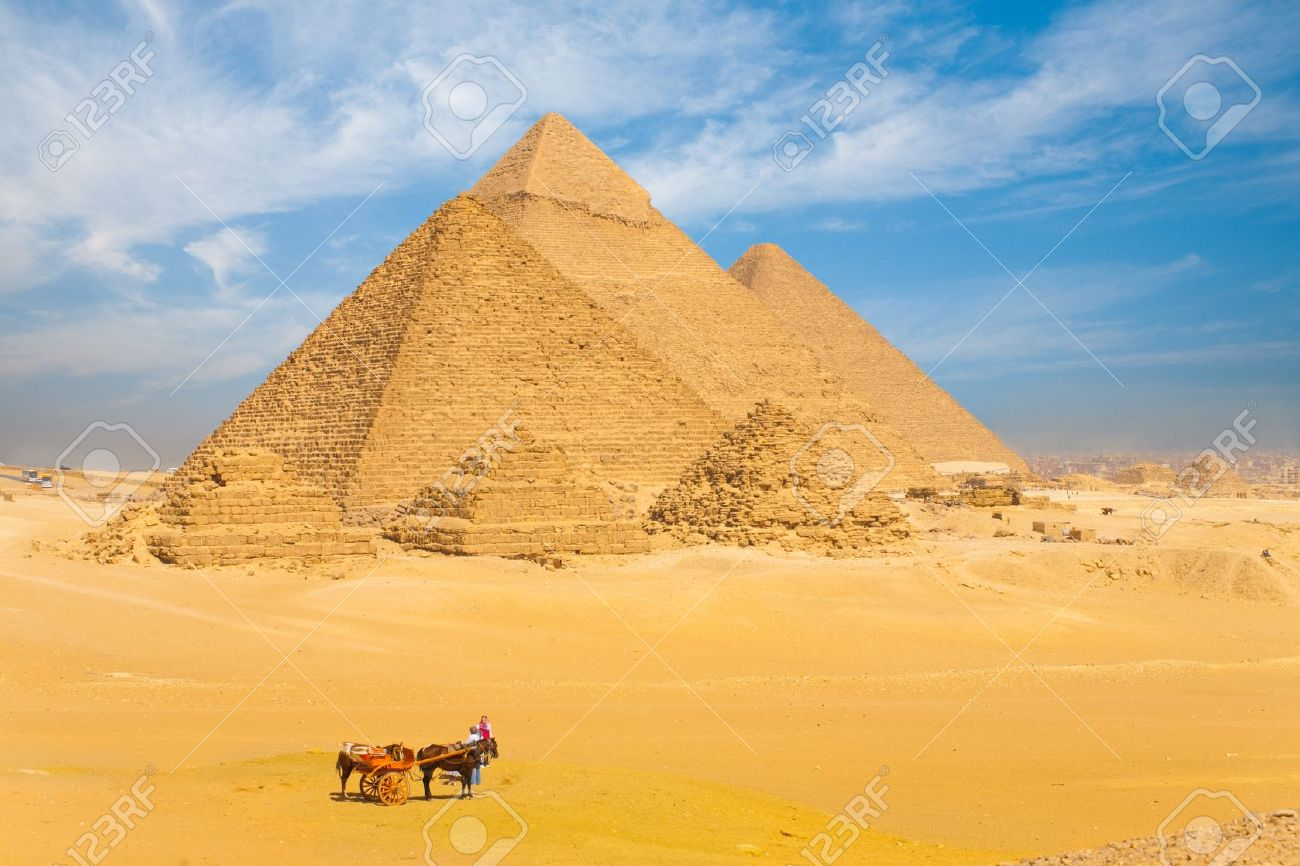 The Giza pyramids lined up in a row against a beautiful blue sky in Cairo, Egypt - 13699767