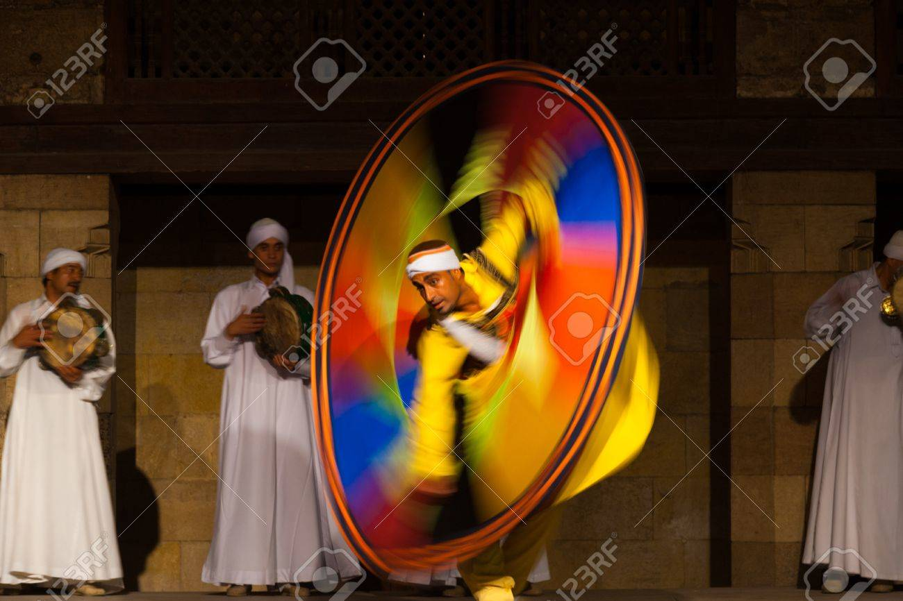 CAIRO, EGYPT - JULY 3, 2010: An Egyptian Sufi dancer in yellow spins during a whirling dervish at an open air courtyard performance, a famous tourist attraction in Cairo, Egypt on July 3, 2010 - 14419626