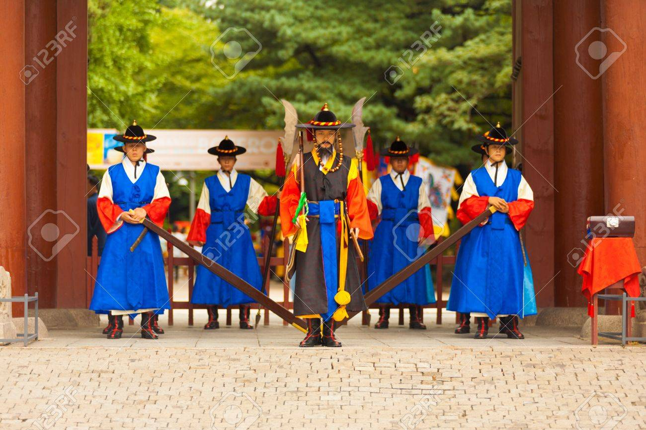 SEOUL, KOREA - AUGUST 27, 2009: Armed guards in traditional costume stand at the entry gate of Deoksugung Palace, a tourist landmark, in Seoul, South Korea on August 27, 2009 - 18831768