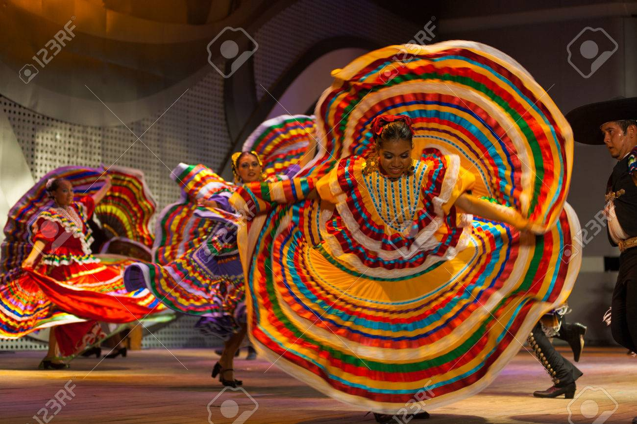 SEOUL, KOREA - SEPTEMBER 30, 2009: An unidentified female Mexican dancer spins and spreads her colorful yellow dress during a traditional folk show at a public outdoor stage at city hall - 25541359