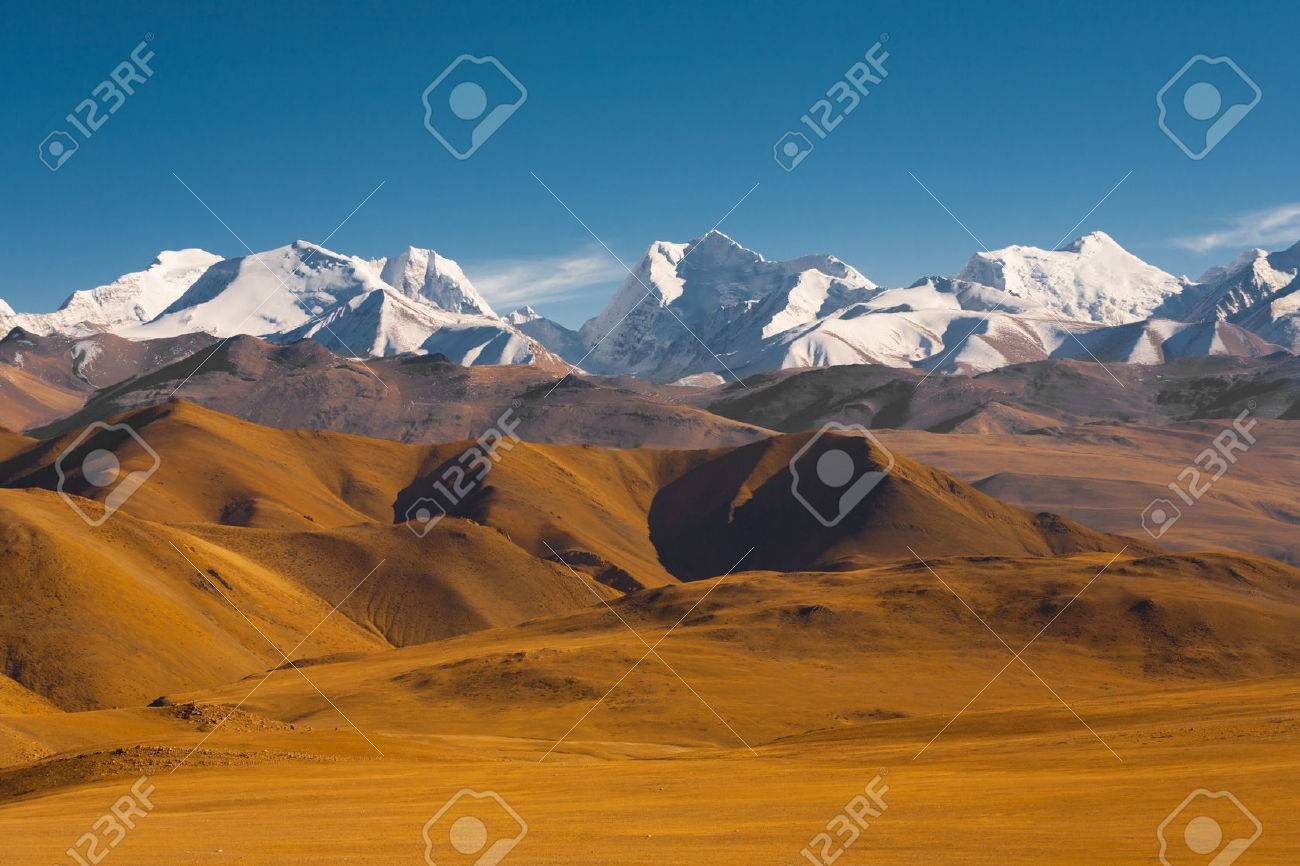 Peaks of the himalayas poke through the beautiful natural landscape of the barren mountainous terrain at the himalayan border between Nepal and Tibet - 26048746