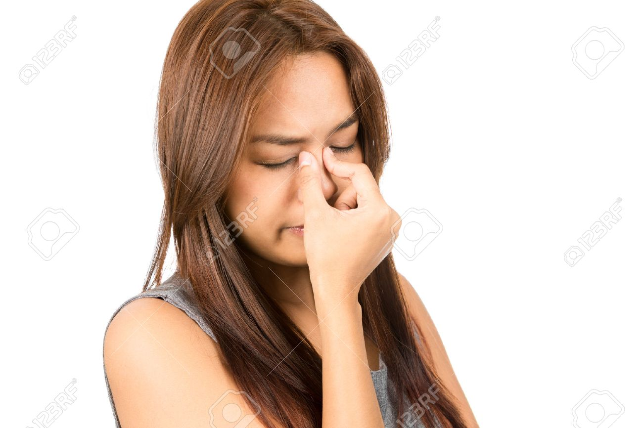 Portrait of suffering Asian woman, light brown hair in sleeveless gray dress pinching bridge of nose in pain and discomfort from sinus congestion, splitting headache. - 44194656